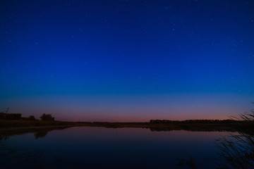 Smooth surface of the lake on a background the starry sky.