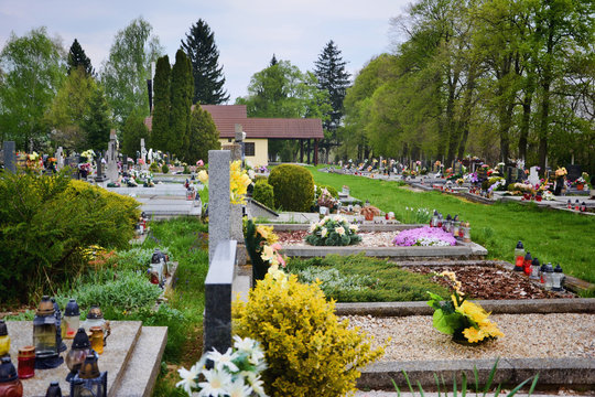 Graves / tombstones in the cemetery / graveyard. All Saints Day / All Hallows / 1st November. Flowers and candles on tomb stone in churchyard. Tvrdomestice/Prasice, Slovakia, Europe