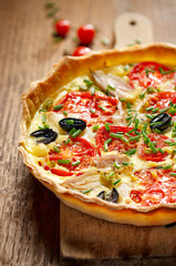 Vegetarian tart with tomato, onion, black olives, fresh chives