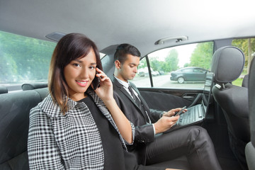 Young business team working together in the car using technology