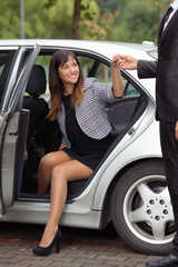 Beautiful young woman stepping out from the car with the assistance of a gentleman
