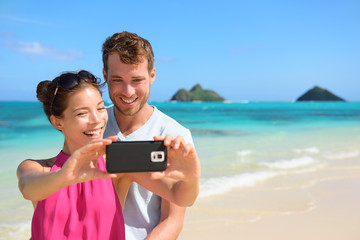 Aufkleber - Beach vacation couple taking selfie on smartphone