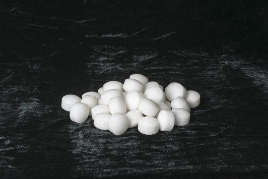 White naphthalene balls on black velvet