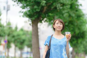 コーヒーカップを持って歩く女性