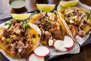 Wall Mural - mexican street tacos with chicken, carnitas and barbacoa beef close up with radish slices