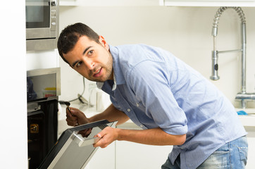 Hispanic male wearing blue shirt in modern kitchen leaning
