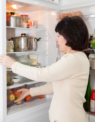 mature woman near   open refrigerator.