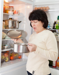 woman checking   food in   refrigerator
