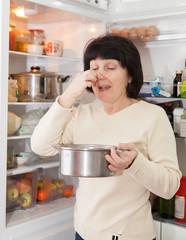 woman near   open refrigerator.