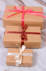 Wrapped gifts for Christmas or other celebration on old wooden background
