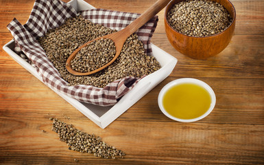 Hemp seeds and oil on wooden background.