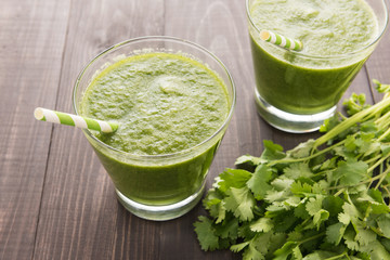Healthy green vegetables and green fruit smoothie on rustic wood