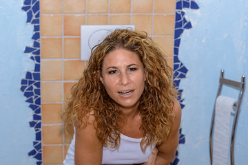 Young woman sitting on the toilet