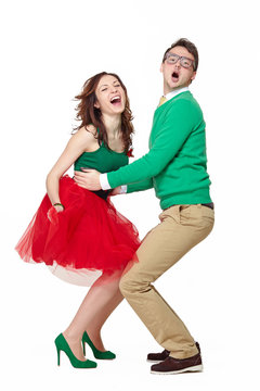 Interracial weird nerd couple dancing together. Caucasian young man wearing eyeglasses and smiling asian woman screaming and wearing 50 style clothes. Fifties nerd concept