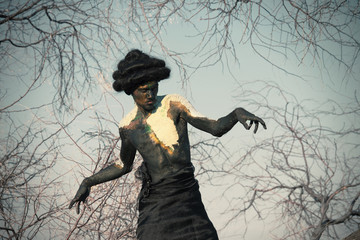Earth spirit. Portrait of a guy in natural body paint with the tree's branches
