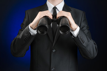 Business and search topic: Man in black suit holding a black binoculars in hand on a dark blue background in studio isolated