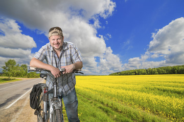 Tourist man standing with a bicycle with road in blooming fields