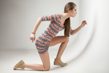 Beautiful young woman posing in dress at studio