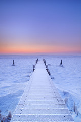 Wall Mural - Jetty on a frozen lake in The Netherlands at sunrise