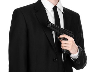 Firearms and security topic: a man in a black suit holding a gun on an isolated white background in studio