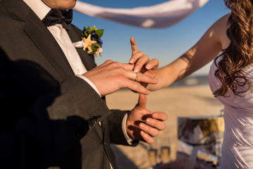 Hands of the groom and bride is wearing a ring on the finger on