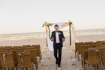 Attractive man is bringing two glasses of champagne on the beach