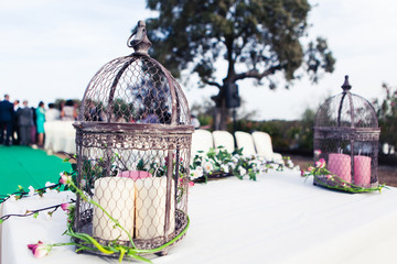 Vintage wedding altar with birdcage, candles and plants. Close up.
