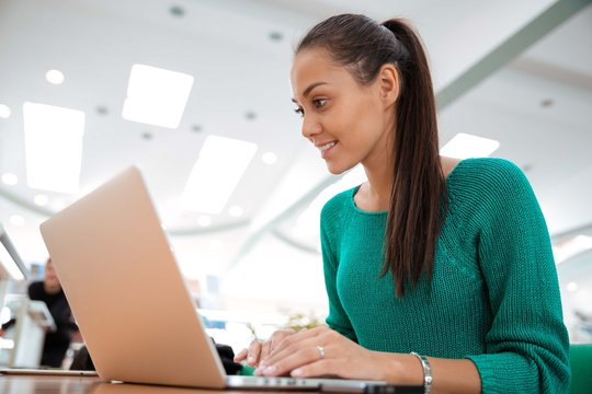 Happy female student using laptop in university
