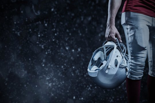 Cropped image of American football player holding helmet against black background