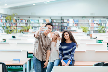 Students making selfie photo on smartphone in the library