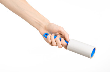 Clean clothes and cleaning the house topic: human hand holding a blue sticky brush for cleaning clothes and furniture from dust isolated on white background in studio.