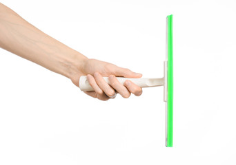 Household cleaning and washing windows theme: man's hand holding a green scraper windows isolated on a white background in the studio.