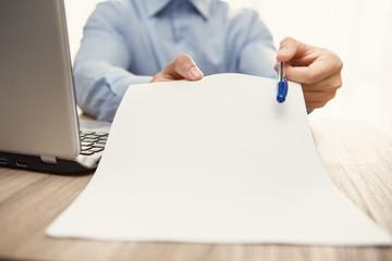 uomo in ufficio con notebook che firma il contratto per assunzione di lavoro