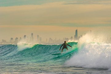 Surfer Surfing a wave with Surfers Paradise in the Background