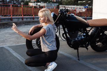 female biker girl making self portrait with vintage motorbike