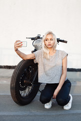 female biker girl making self portrait with vintage motorbike