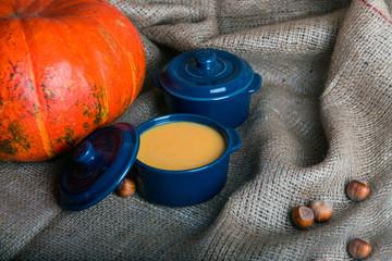 pumpkin soup in a bowl on sackcloth napkin