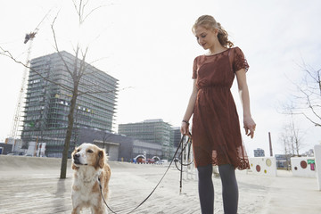 Young woman standing in the playground with her dog, Munich, Bavaria, Germany