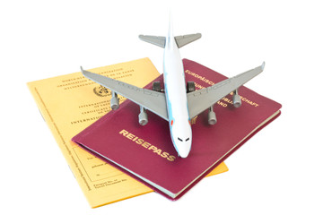 Flugzeug auf Reisepass und Impfausweis