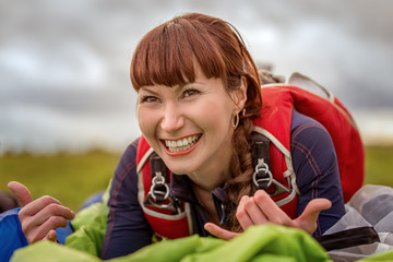 Redhead young woman smiling while lying on the green parachute