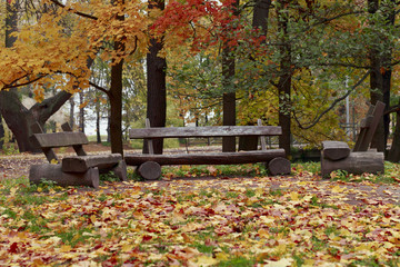 Three wooden benches in the autumn park.