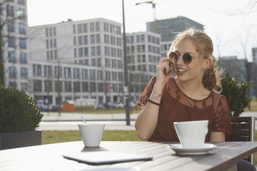 Young woman talking on a mobile phone at sidewalk cafe, Munich, Bavaria, Germany