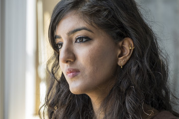 Portrait of a young middle eastern woman, looking out a window, concerned expression