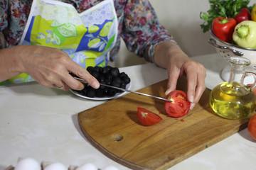 The woman cuts a tomato