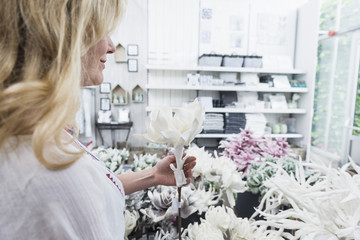 Mature woman shopping for artificial flower in garden centre, Augsburg, Bavaria, Germany