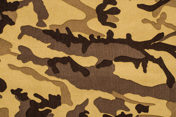 Camouflage pattern on fabric. Brown khaki military texture background