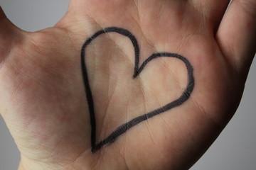 schwarzes Herz auf der Hand