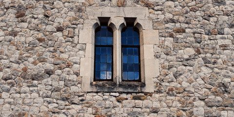 Old stone medieval wall with two windows in center