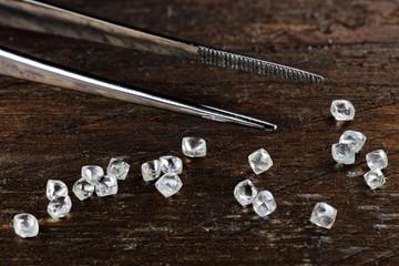 echte Rohdiamanten mit Pinzette auf rustikalem Holzhintergrund