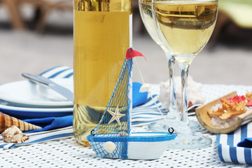 Served table with wine bottle and little boat